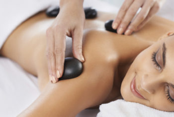 A young woman having hot stone therapy